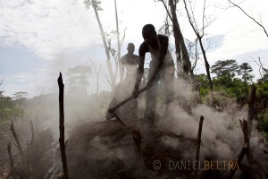 Men work on a makeshift kiln that produces charcoal out of rainforest wood near Bikoro, Democratic Republic of Congo.