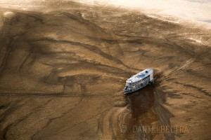 A traditional river boat and its crew are stranded on a sand bank during one of the worst droughts ever recorded in the Amazon. Barreirinha, Amazonas State, Brazil.